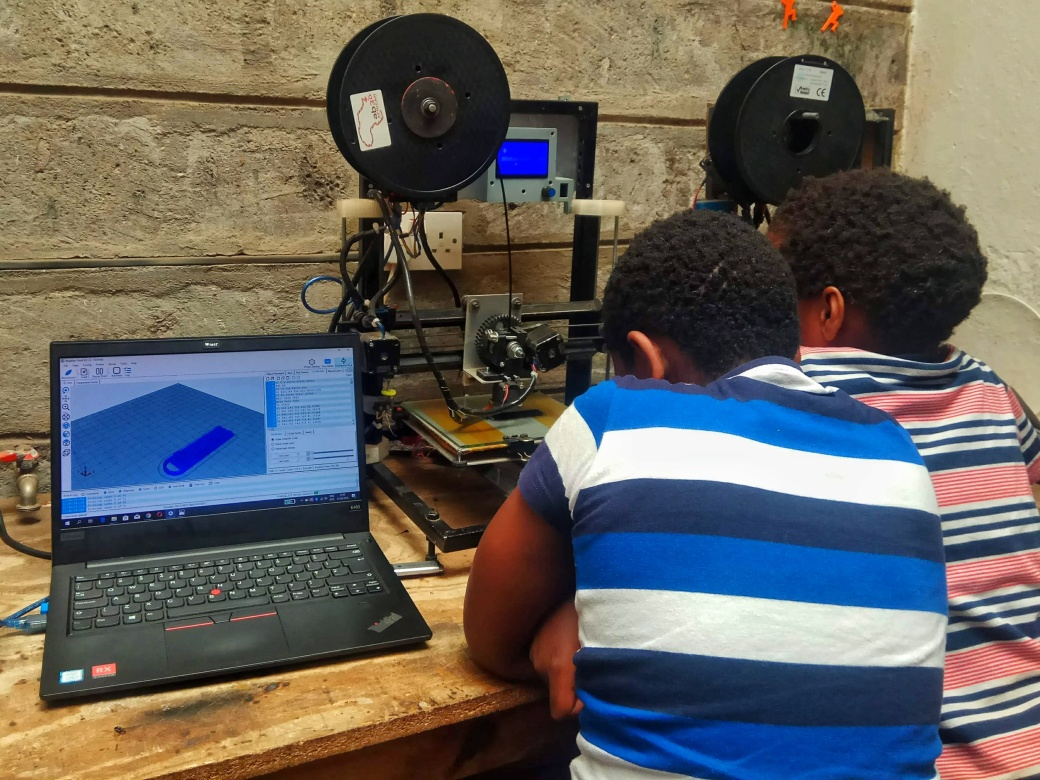 A pair of children watching a 3D printer in action