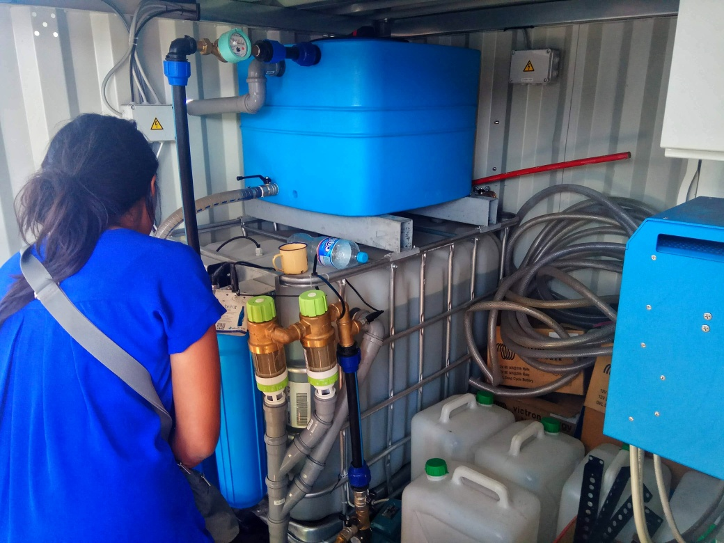 Jodie inspecting the water purification unit inside an OffGridBox