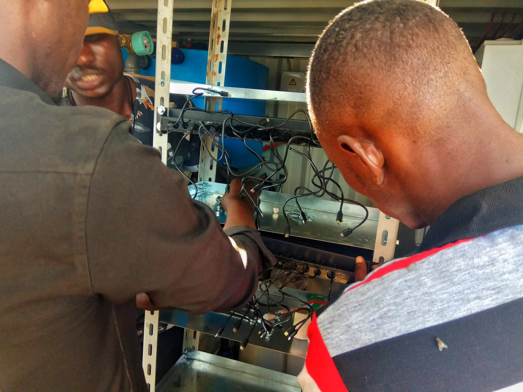 Two men installing charging cables to supply power to the community
