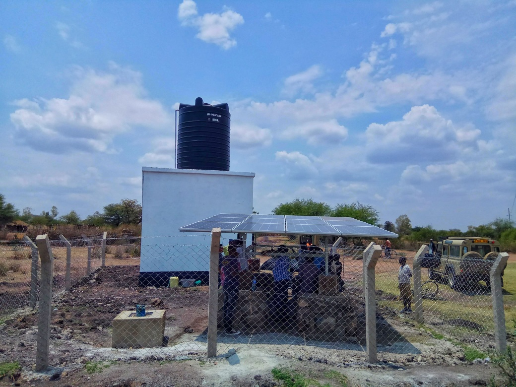 A newly installed set of solar panels next to a well with a pump and water tower