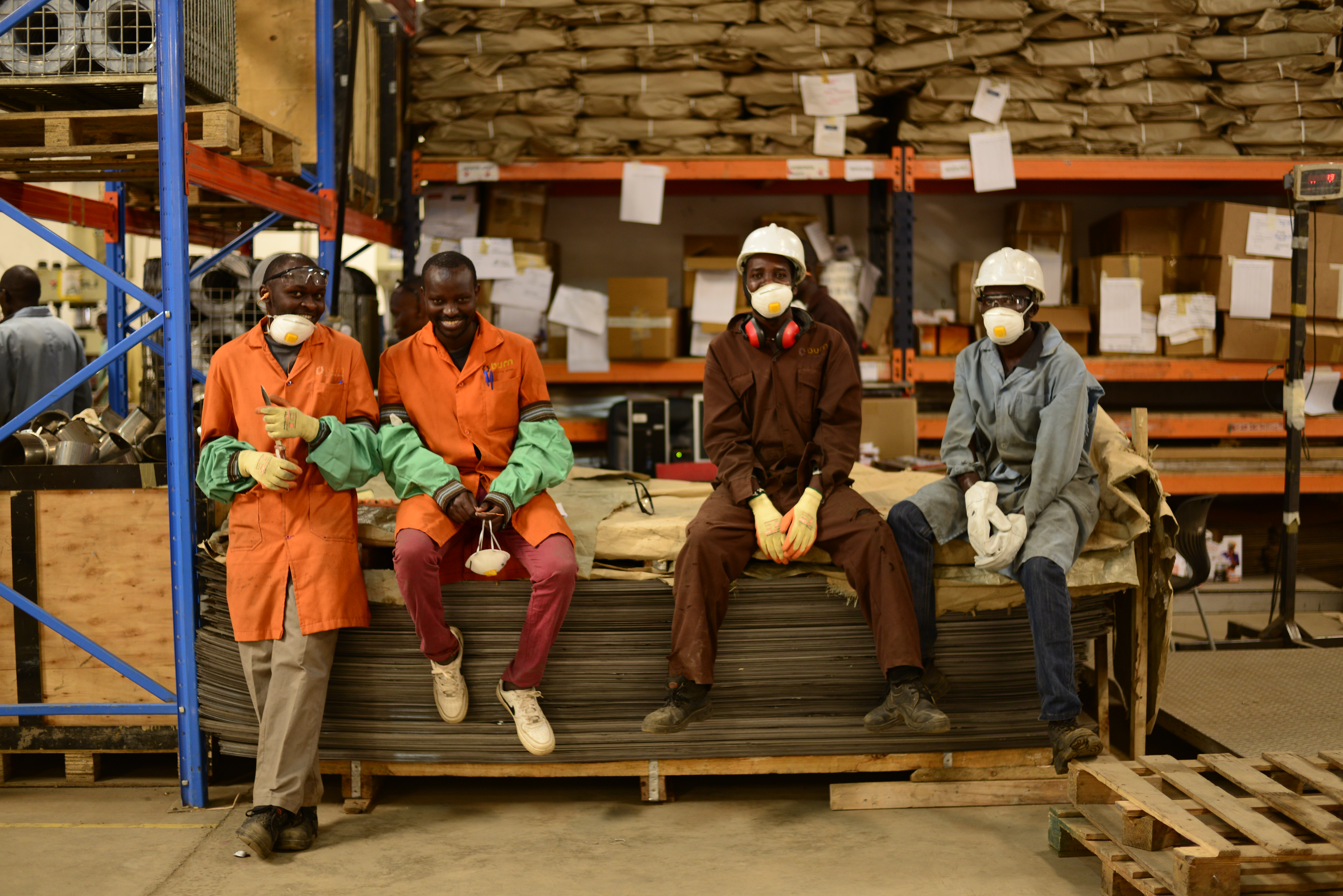 Workers smiling as they take a break on the factory floor