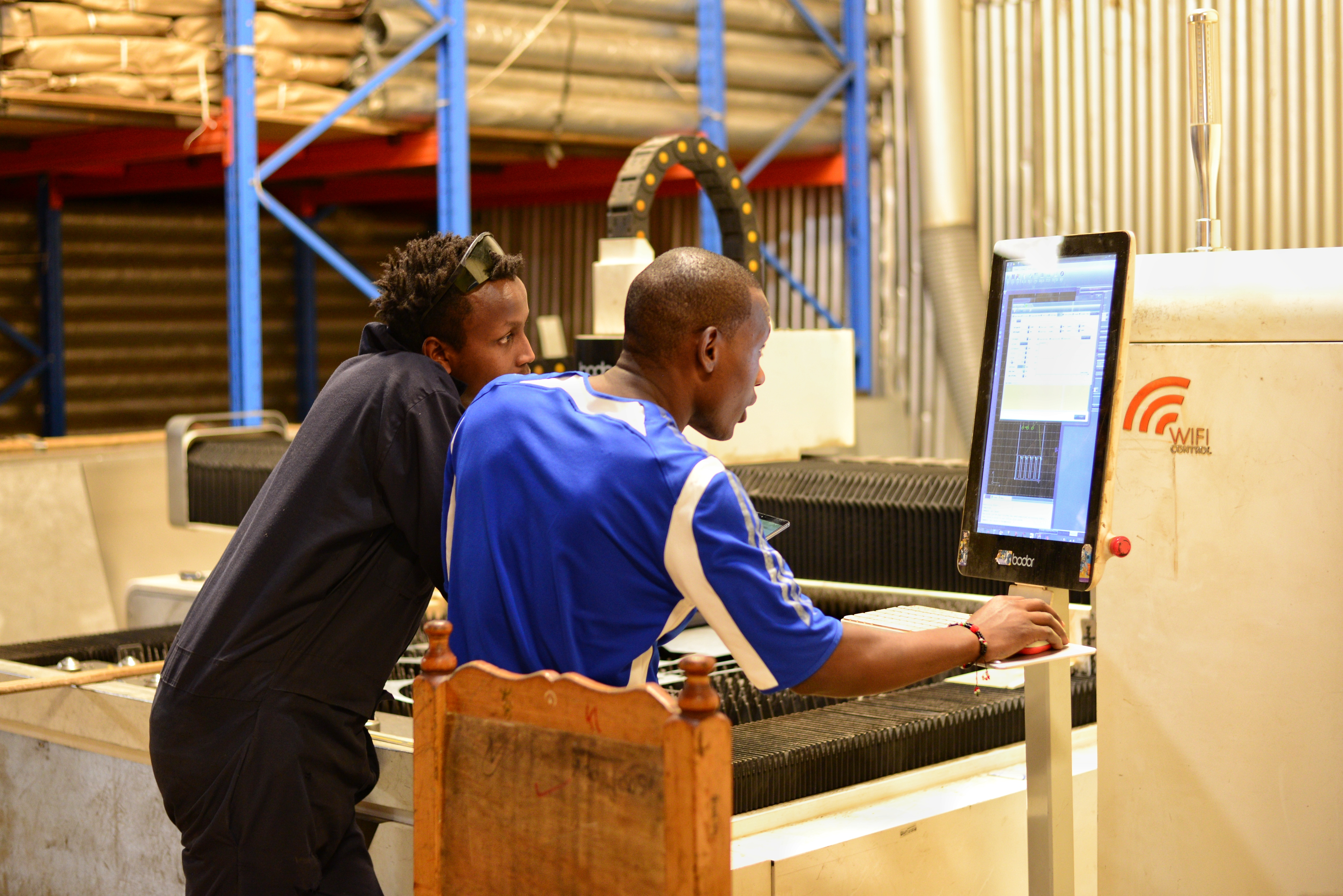 Two design engineers inputting a job on a CNC machine