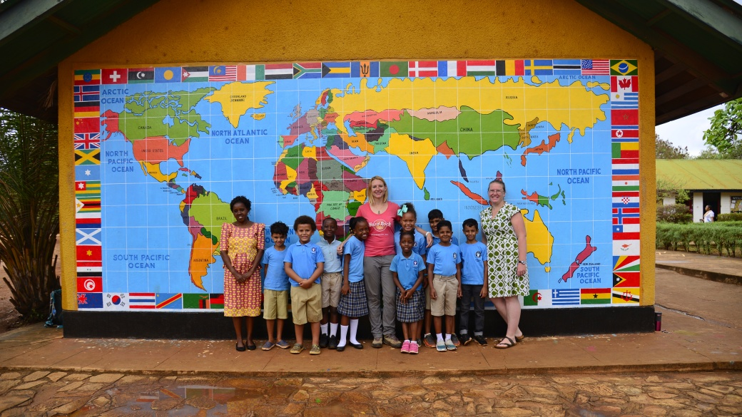 Me with a Year 3 class and teachers in front of a mural with a world map